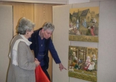 Team member Gill Winfiled pointing out embroidery detail to a visitor